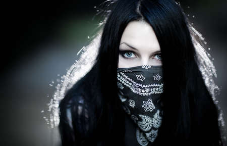 hoodlum: Young woman hooligan with scarf portrait. Dark dramatic colors. Stock Photo