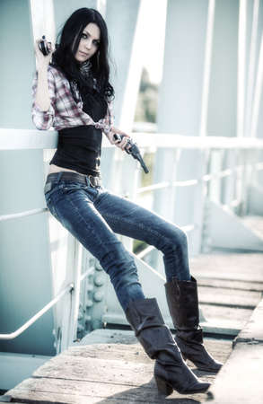 Young slim woman with guns on a bridge. photo