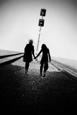 2 persons: Two goth women walking far on railway. Black and white concept.