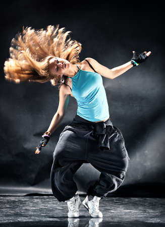hiphop: Young woman modern dance. Dark grungy background. Stock Photo