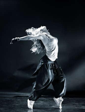 hip  hop: Young woman modern dance. Dark blue tint.
