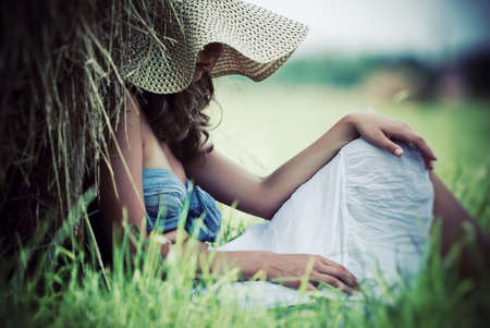 Young pensive woman resting on a field. photo