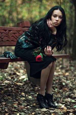 Slim brunette woman in a park. Autumn sadness concept. photo