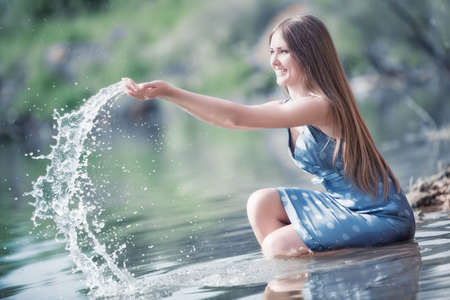 Young woman on a river bank playing with water. White and blue colors. photo