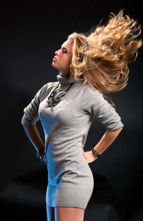 Young woman with fluttering hair. On dark background. photo