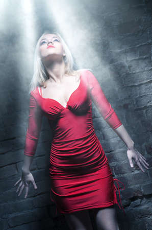 Young woman in red dress standing under the bright cold light. photo