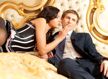 Young couple on a bed. Golden colors. photo