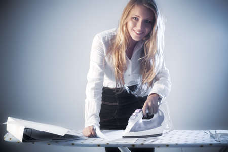Young businesswoman iron paper documents. Soft blue colors. photo
