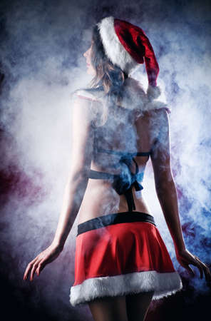 Young woman in santa clothing. Dark contrast colors. photo
