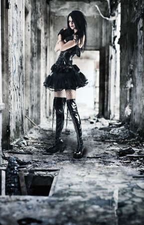 Young goth woman in ruined building. Contrast colors. photo