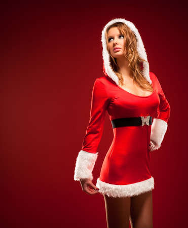 Young sexy woman in santa clothing. On red background. photo
