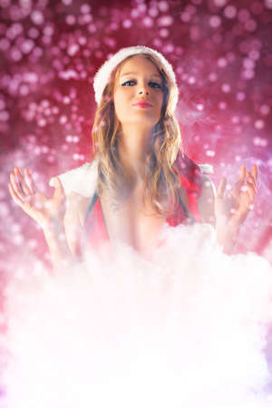 Young fairy woman in santa clothing with smoke effect. photo