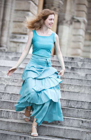 Young woman in dress running down on stairs. Stock Photo - 6077339
