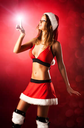 Young sexy woman in santa clothing setting the star. photo