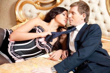 Giovane coppia su un letto. Colori dorati saturi