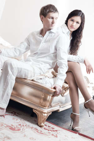 Young couple in a bedroom. Bright white colors. photo