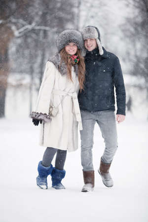 Young couple walking in a park. Winter season. photo