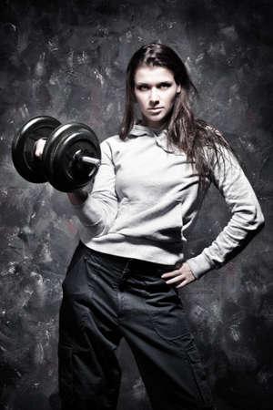 levantamiento de pesas: Ejercicios de deporte de la joven mujer fuerte. Colores de contraste.