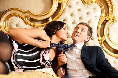 mujer con corbata: Mujer joven tirando de hombre en la cama. Colores saturados de oro.  Foto de archivo