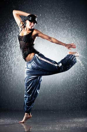 rain shower: Young woman modern dance. Water studio photo.