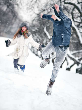 pursue: Young couple playing outdoors. Winter season. Stock Photo
