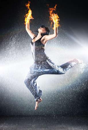 Jonge vrouw moderne dans. Studio foto water en vuur effect.