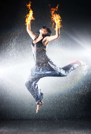 Young woman modern dance. Water studio photo and fire effect. photo