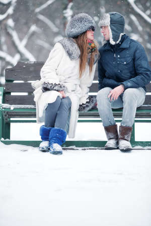 Young couple in love sitting on a bench in a park. photo