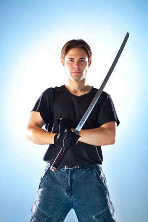 hombre fuerte: Hombre fuerte con espada de samurai. Sobre fondo azul suave.