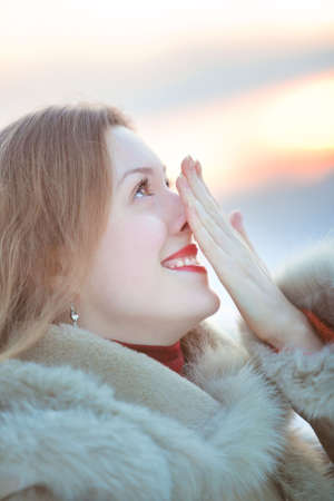 rubbing noses: Young woman winter portrait. Rubing her nose. Stock Photo