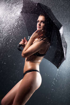 Young woman with umbrella under the rain. Water studio photo. photo