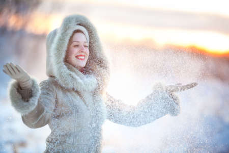 fur hood: Young happy woman throwing up snow.