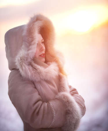 Young woman winter portrait. Red sunset light. photo