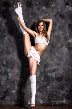 Young sexy woman stretching up leg on dark wall background. photo