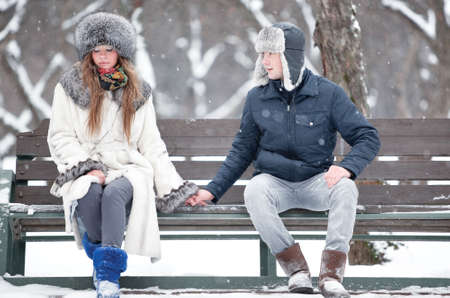 shy girl: Young couple sitting on a bench in a park. Stock Photo