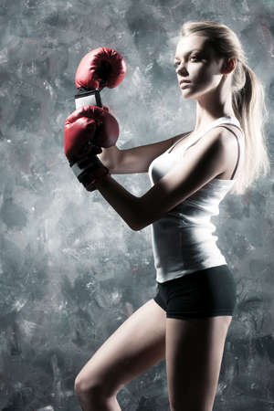 punched: Boxer woman fashion. On wall background. Stock Photo