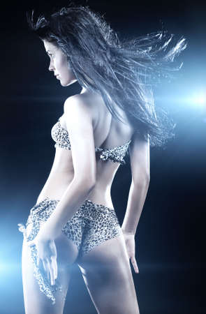 Young sexy dancing woman. Blue tint.