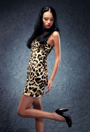 Young woman studio fashion. On wall background. photo