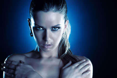 Young woman serious portrait. Cold blue tint. photo