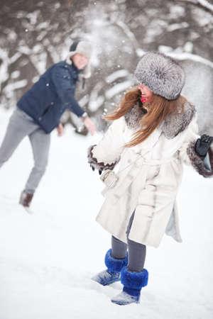actividades recreativas: Joven pareja jugando al aire libre. Temporada de invierno. Foto de archivo