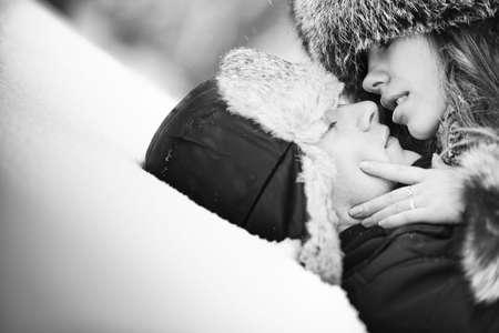 hombres besandose: Joven pareja bes�ndose en la nieve. Blanco y negro.