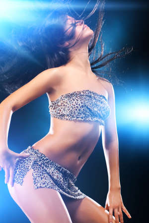 Young sexy dancing woman. On dark background with flashes effect.