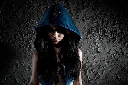 Young woman with hood on head. Dark contrast colors. photo