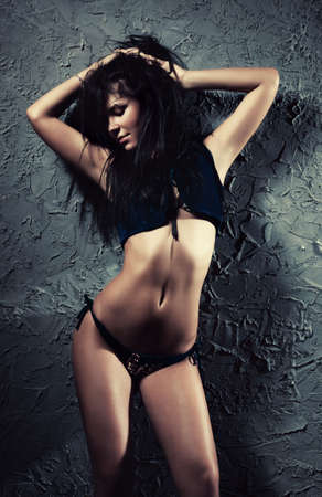 Young sexy brunette woman. On wall background. photo
