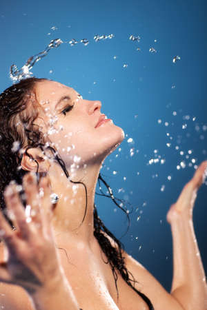 Young woman washing face. On blue background. photo