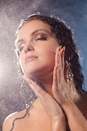 Young woman face with water spray. photo