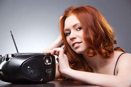 Young woman listening radio. On gray wall background. Stock Photo - 6678129