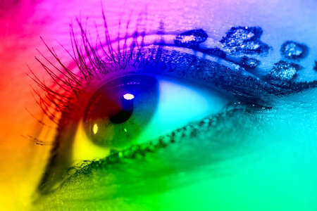 tint: Young woman eye closeup. Spectrum colors effect. Stock Photo