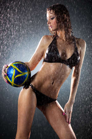 Young sexy woman football player. Water studio photo. photo