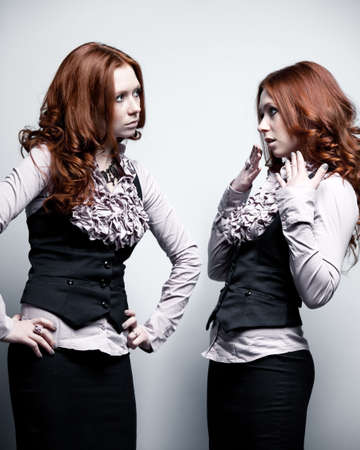 role models: One woman in two roles. On gray wall background. Stock Photo